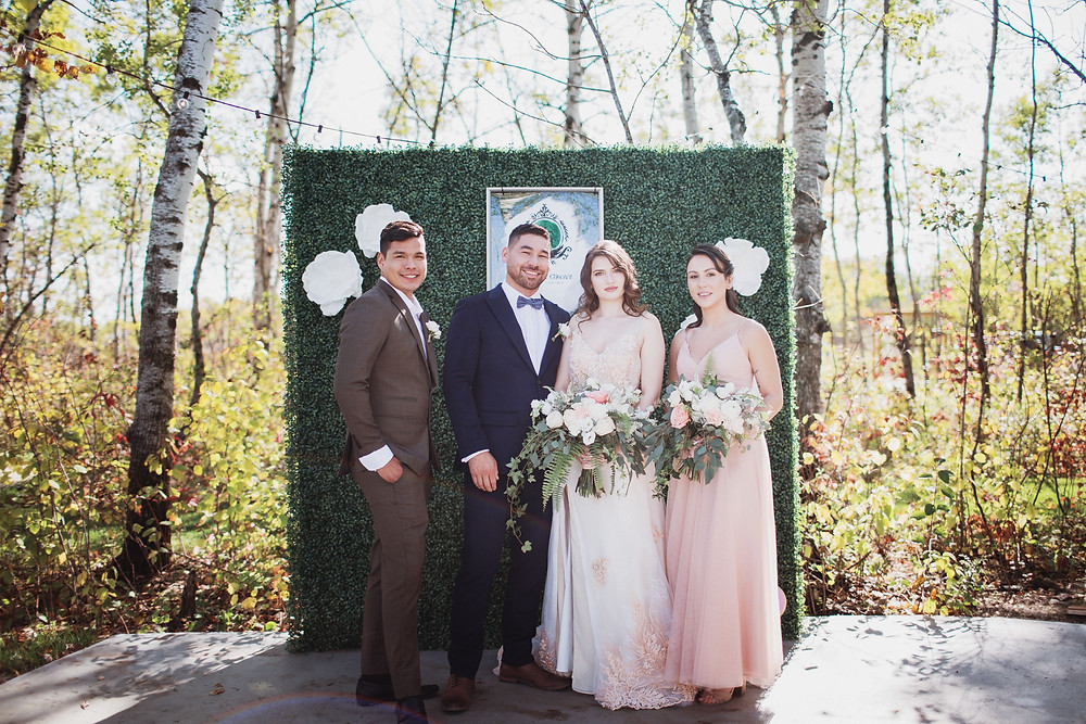 Bridal party poses in front of photo greenery backdrop