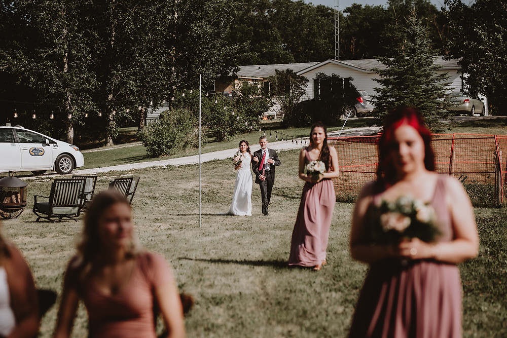 Bride and father walking from house to backyard ceremony space.