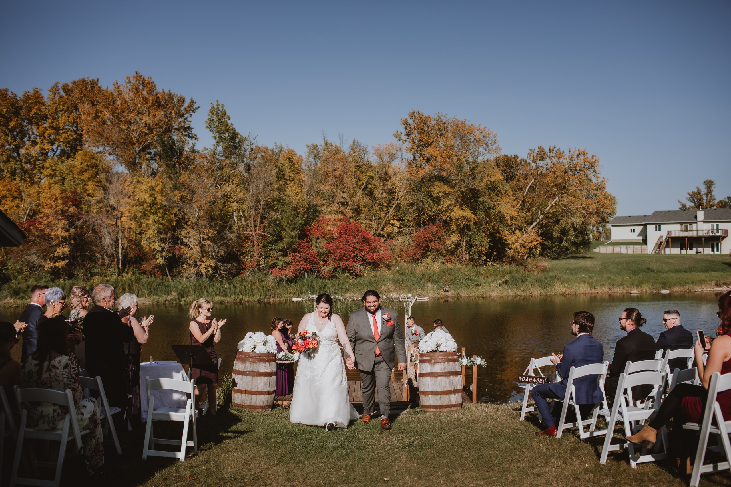 Wedding Couple Exits fall wedding ceremony overlooking the water.