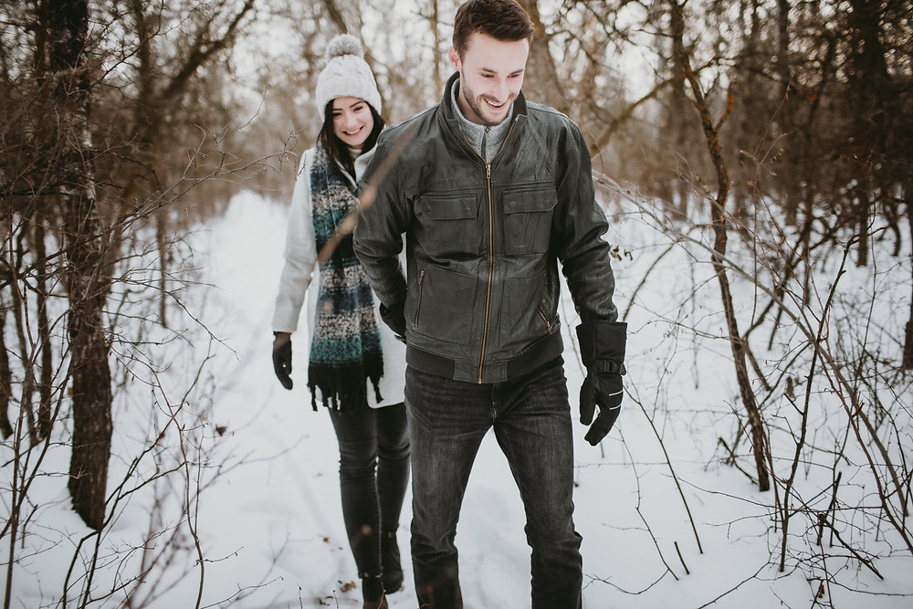 Engaged couple walks through forest during winter engagement photos.