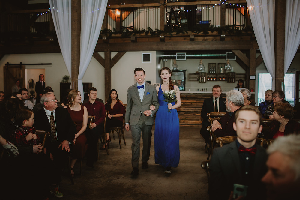 Bridesmaid in royal blue gown and groomsman in grey suit walk down aisle.