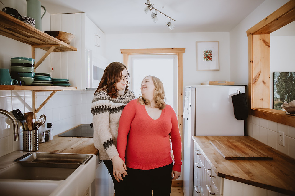 Couple poses in kitchen of rented cabin in Gimli, Manitoba.