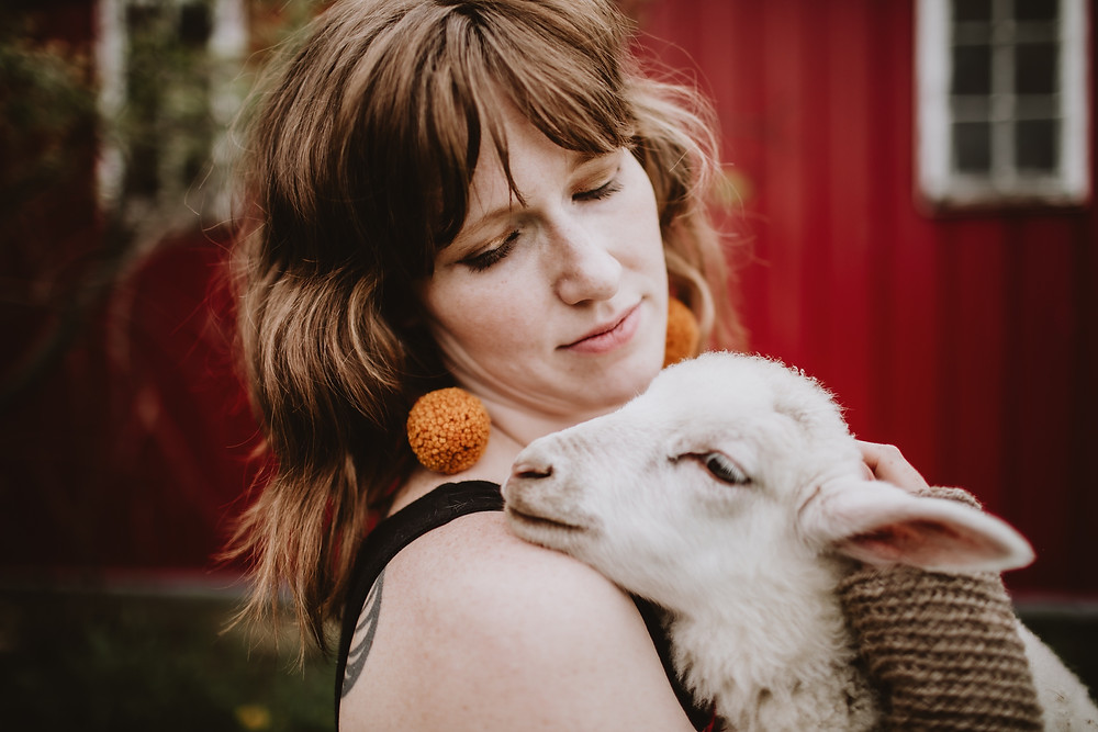 Lamb poses with wool, pom earrings.