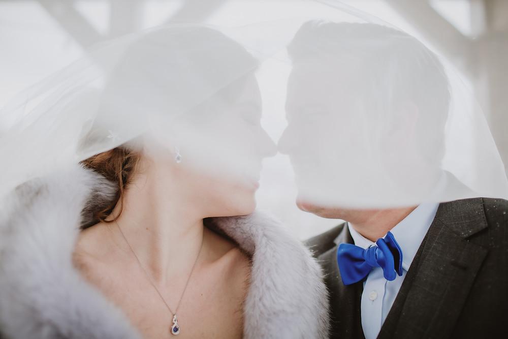 Bride and groom under wedding veil.