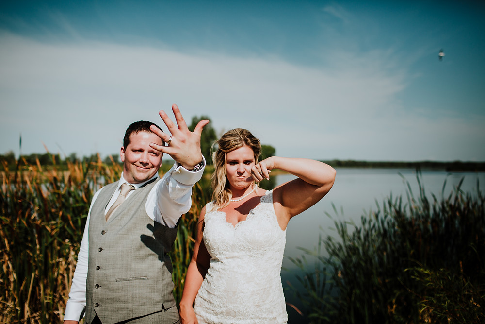 Bride and groom pose in front of Grand Beach, MB marsh, displaying their wedding bands.