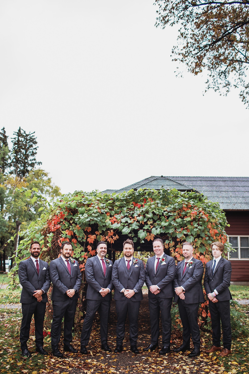 Groom and groomsmen in black suits with red boutonnieres.