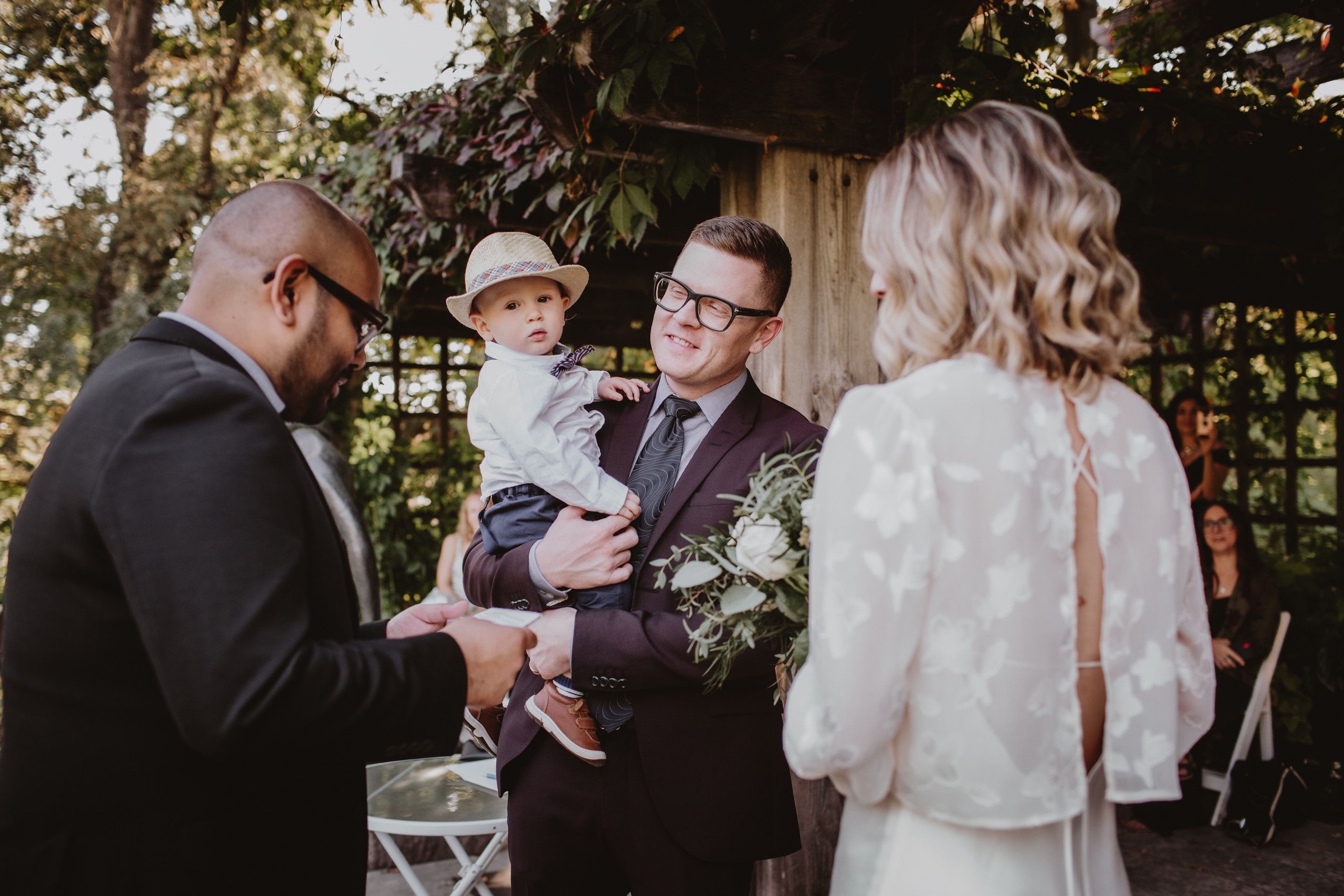 Groom Hold Son during wedding ceremony in Assiniboine Park.