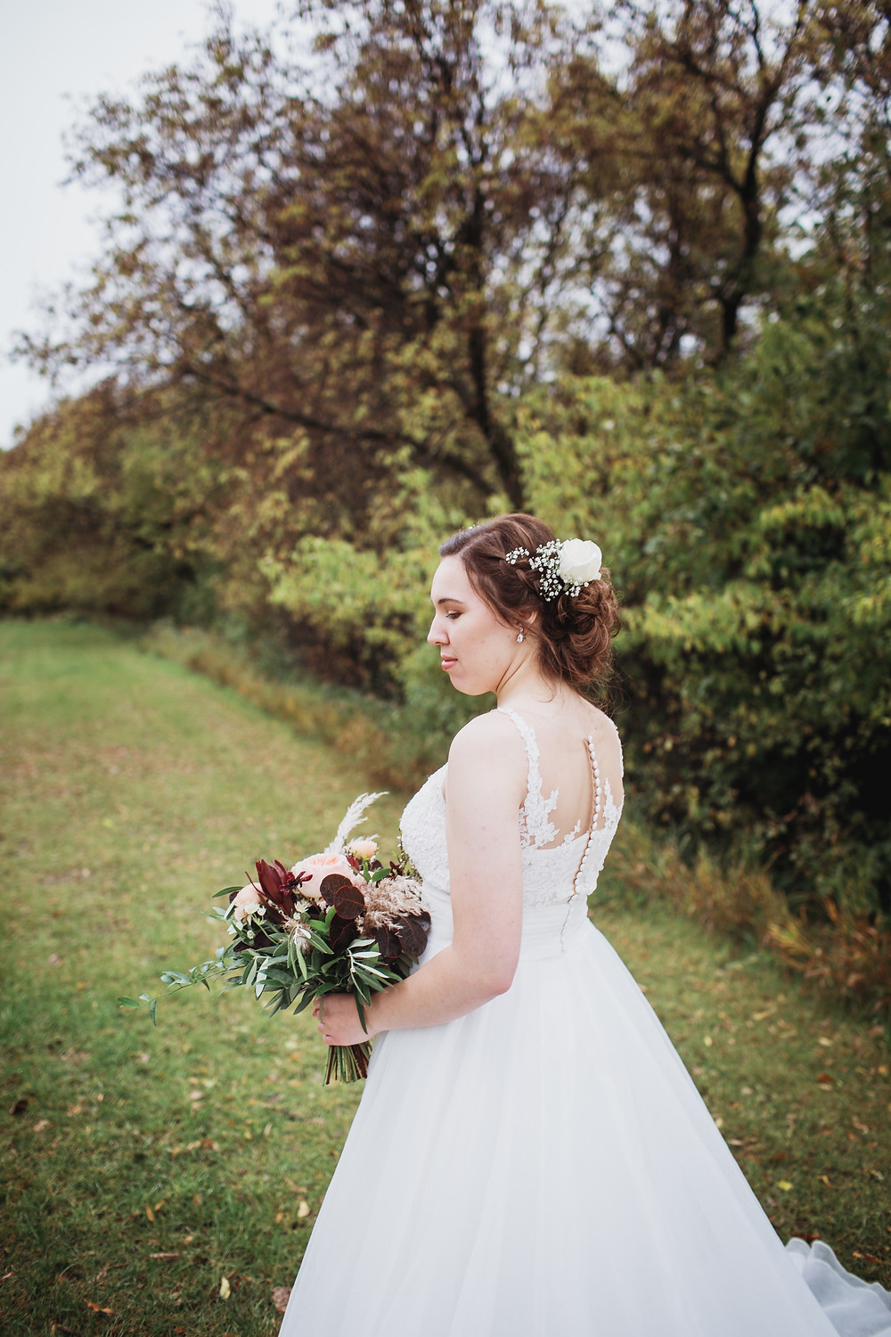 Bride looks over shoulder during her rainy fall wedding day.