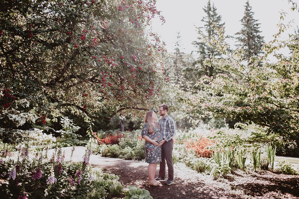 Couple poses in stunning morning light during garden, maternity photo session.