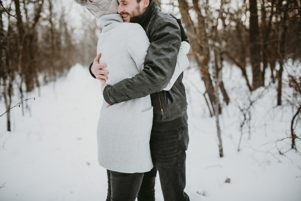 Fiances embrace during winter couples photos.