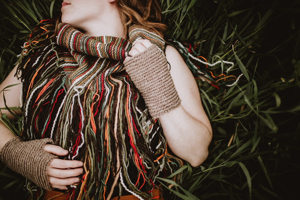 Multicoloured scarf with fringe and light brown fingerless gloves.