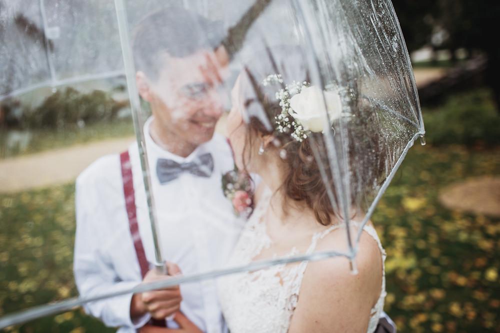 Bride and groom cuddle under umbrella during rainy fall wedding.