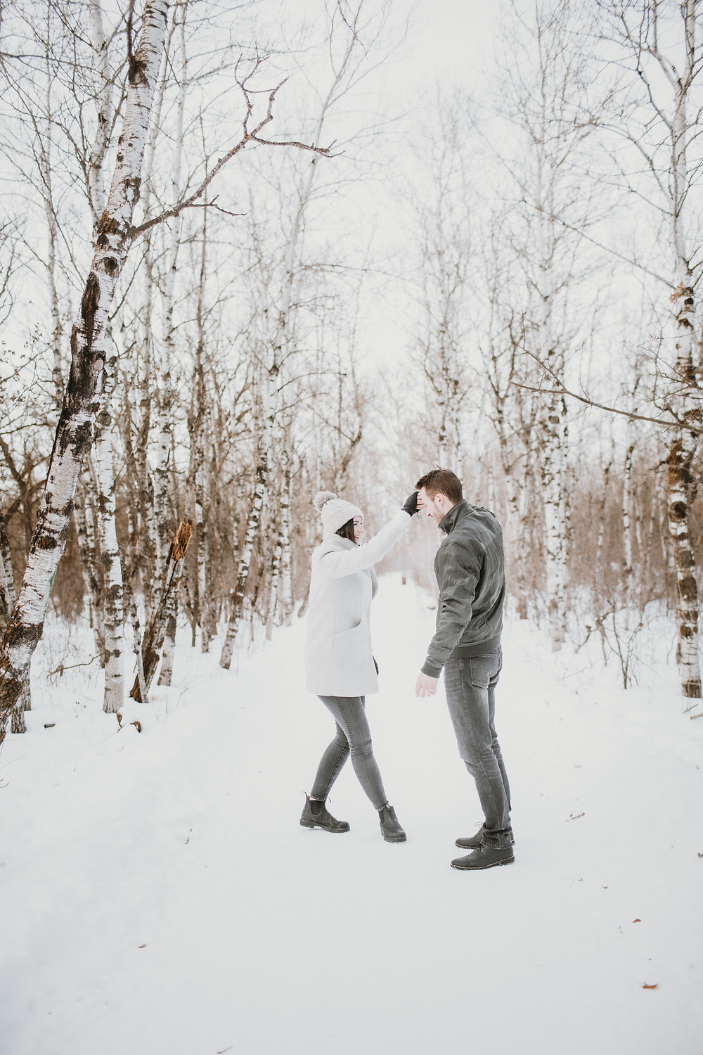 Engaged couple dances during they snowy engagement session.