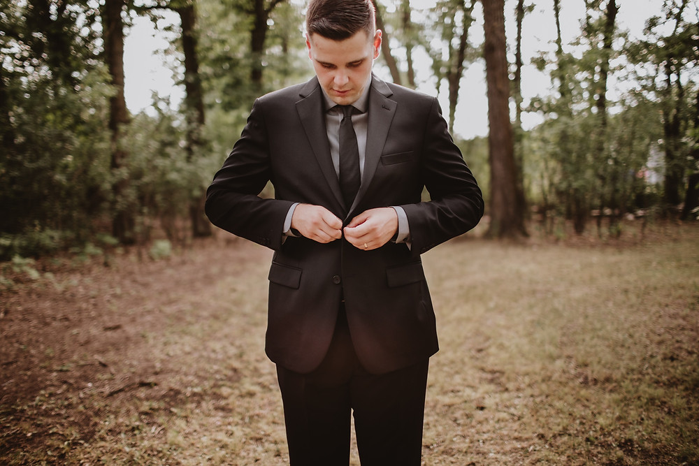 Groom buttoning suit jacket.