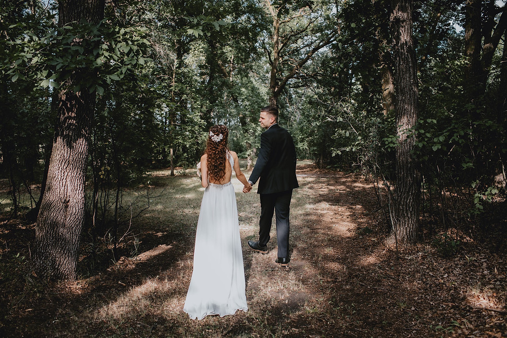 Groom lead bride through the woods on their property.