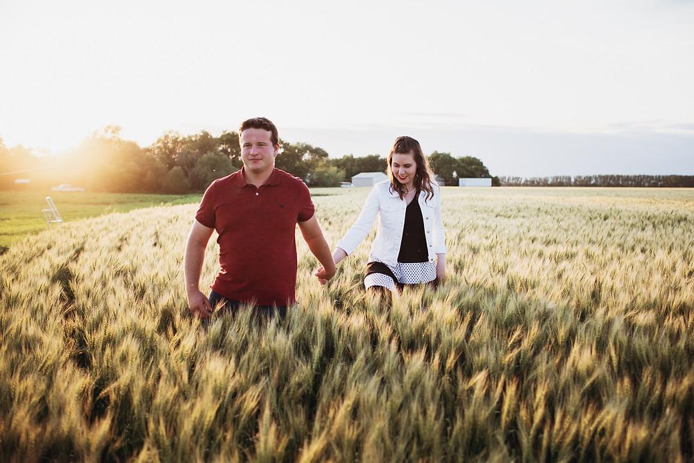Couple walks hand-in-hand through their wheat field.