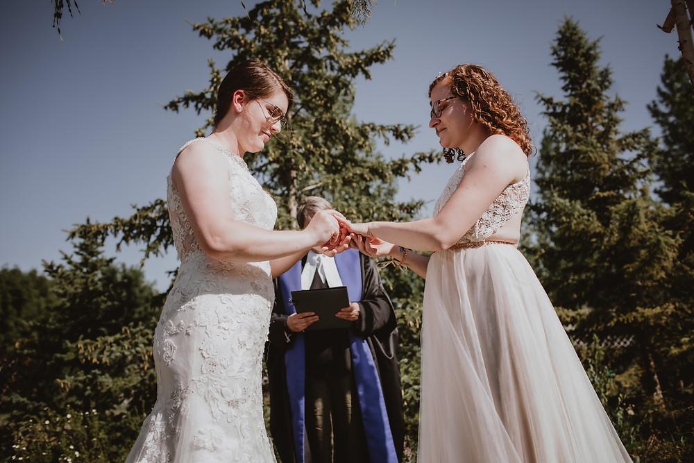 Brides exchange rings during intimate micro-wedding.