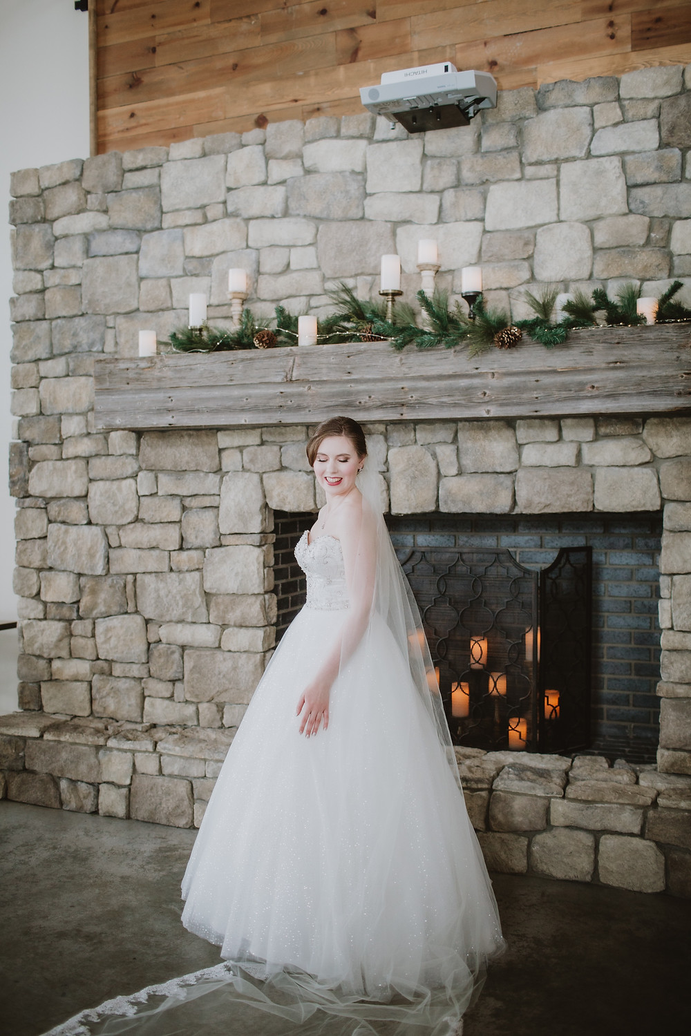 Manitoba bride poses in front of fireplace at Hawthorne Estates.