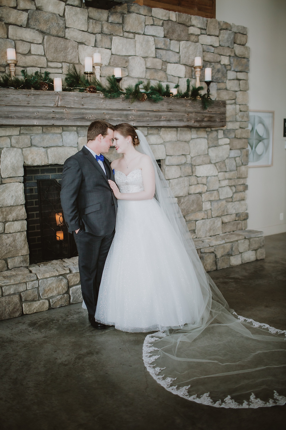 Canadian bride and groom pose in front of fireplace for wedding portraits.
