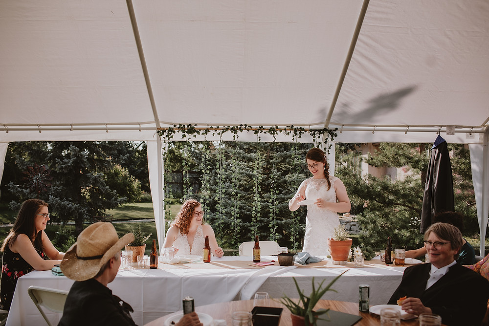 Brides enjoy pizza and beer after micro-wedding.