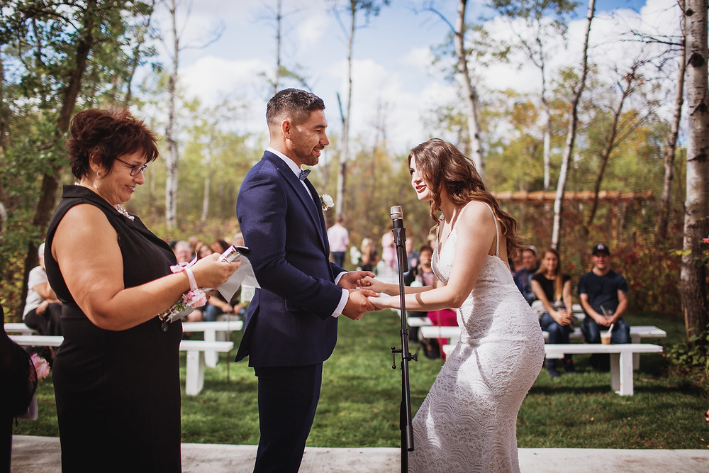 Open air wedding ceremony at Kinloch Grove, in Manitoba. Wedding gown by Anna Lang Bridal. Suit by Eph Apparel. Officiant A Perfect Ceremony I Do.