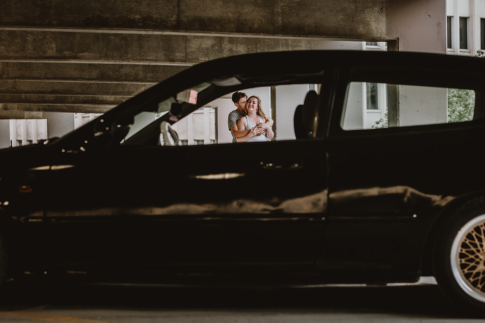 Couple poses, framed by black car.