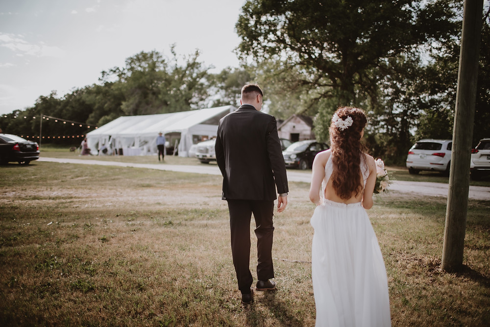 Bride and groom walking towards their tented reception.