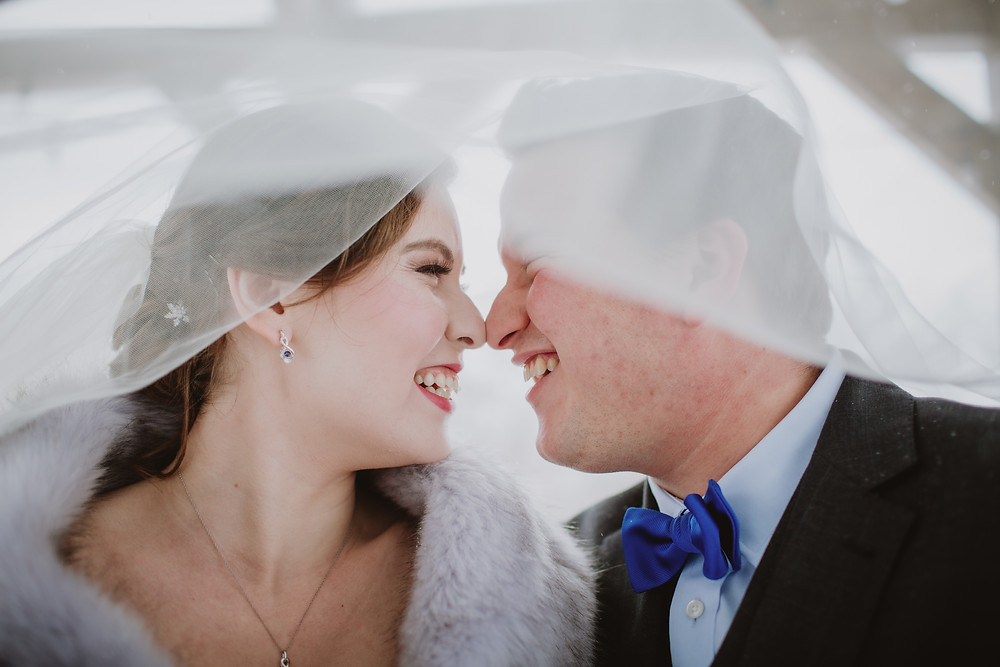 Winter bride and groom touch noses under veil.