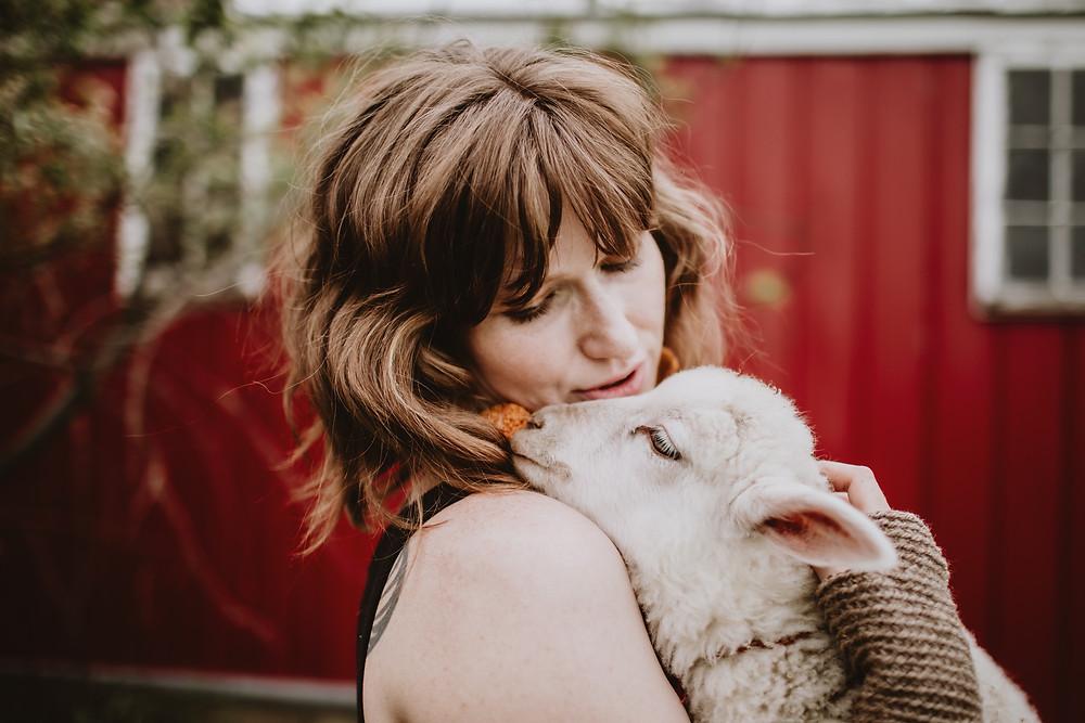 Lamb snuggles on shoulder.