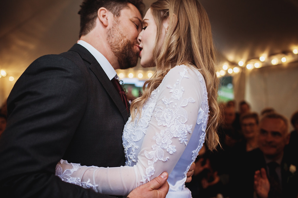 Bride and groom kiss during ceremony.