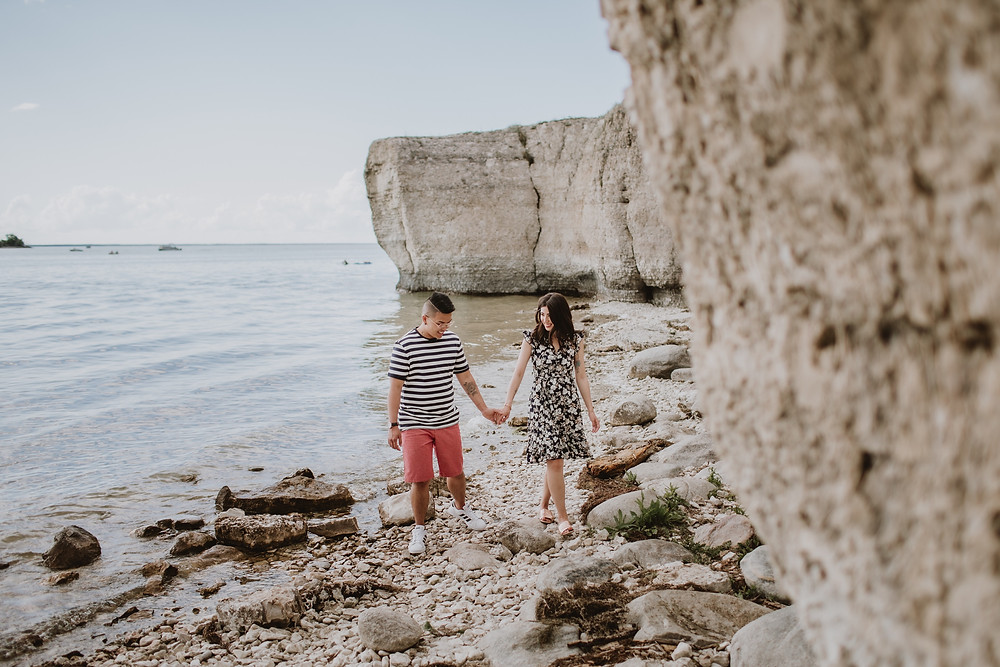 Couple walks along the rocky beach of Steep Rock, Manitoba.