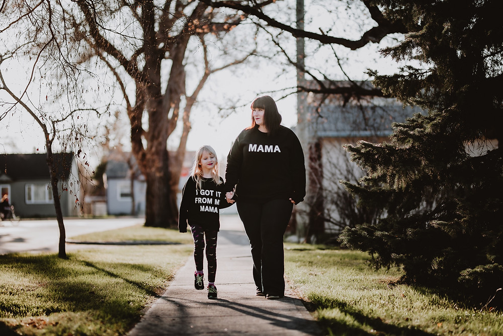 Mom and daughter walk hand-in-hand down their street.