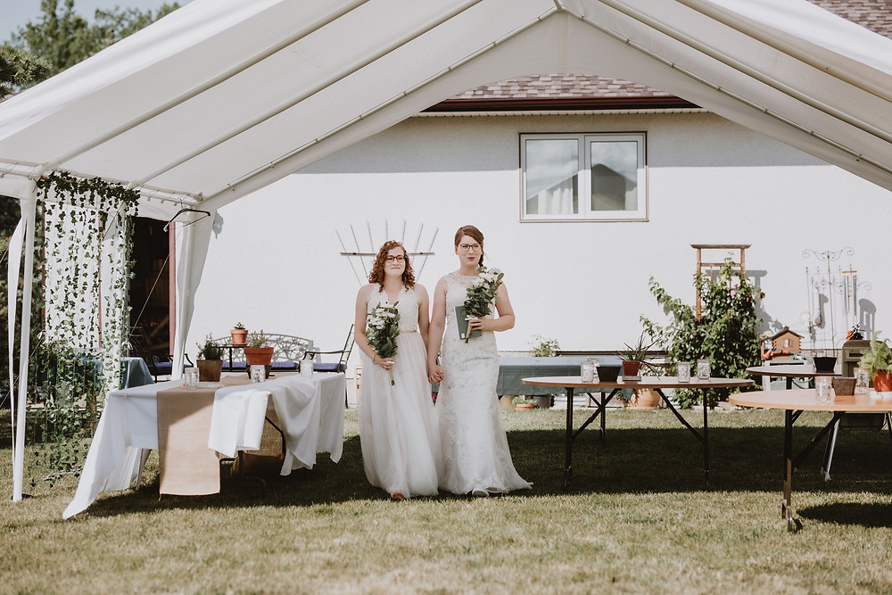 Brides walk from house to ceremony space in backyard.