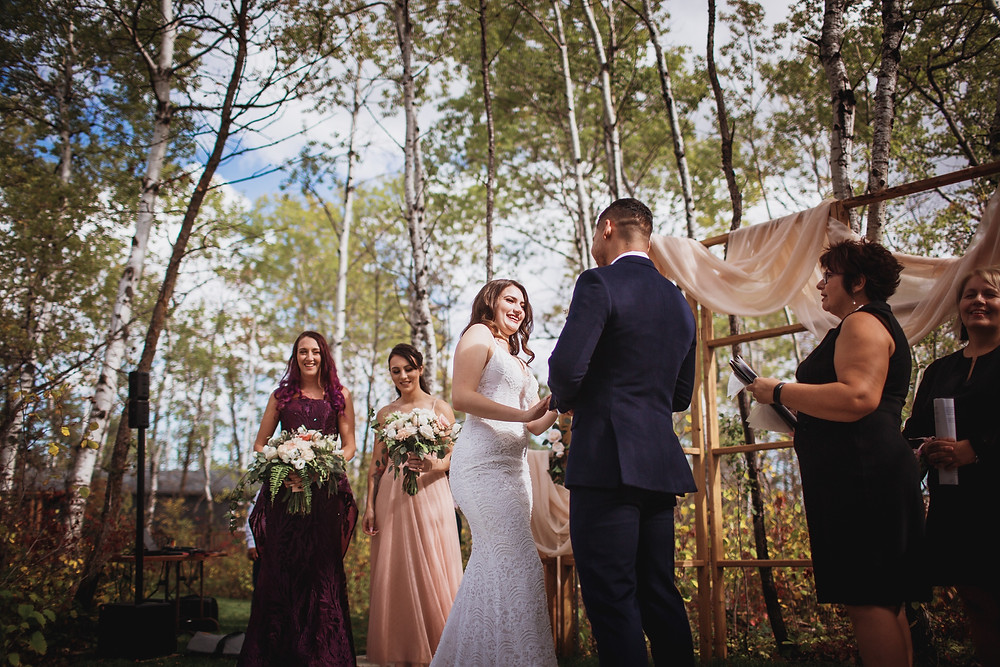 Open air wedding ceremony at Kinloch Grove, in Manitoba. Wedding gown by Anna Lang Bridal. Suit by Eph Apparel. Bridesmaid dress from Pearl and Birch. Flowers by Yellowbirch Florals. Officiant A Perfect Ceremony I Do.