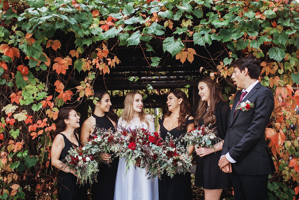 Bride and her attendance in black gowns and suit, with red flower bouquets.