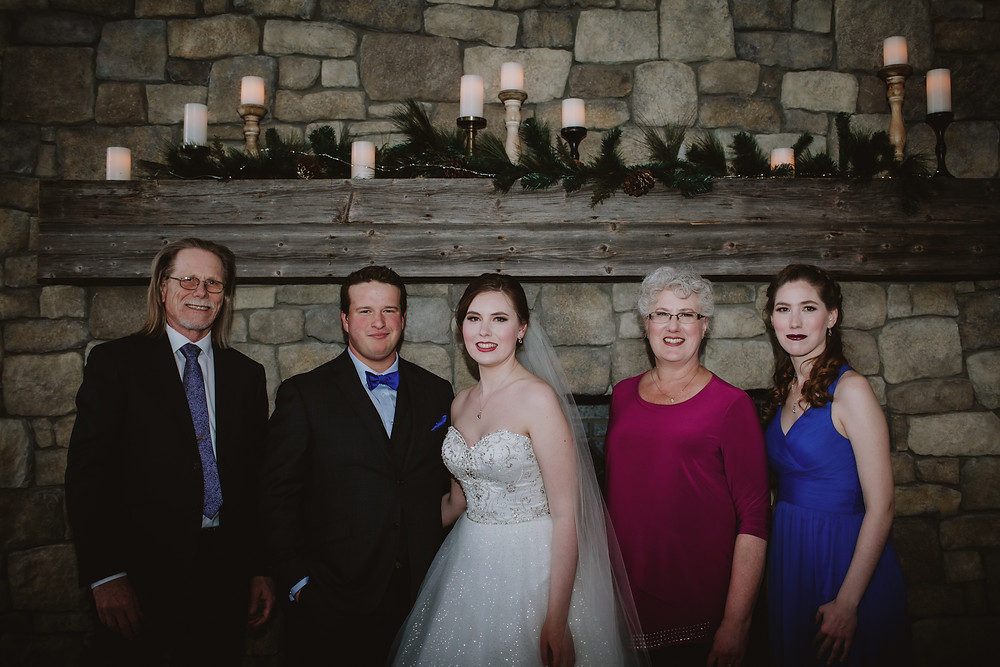 Family wedding day portrait in front of fireplace.
