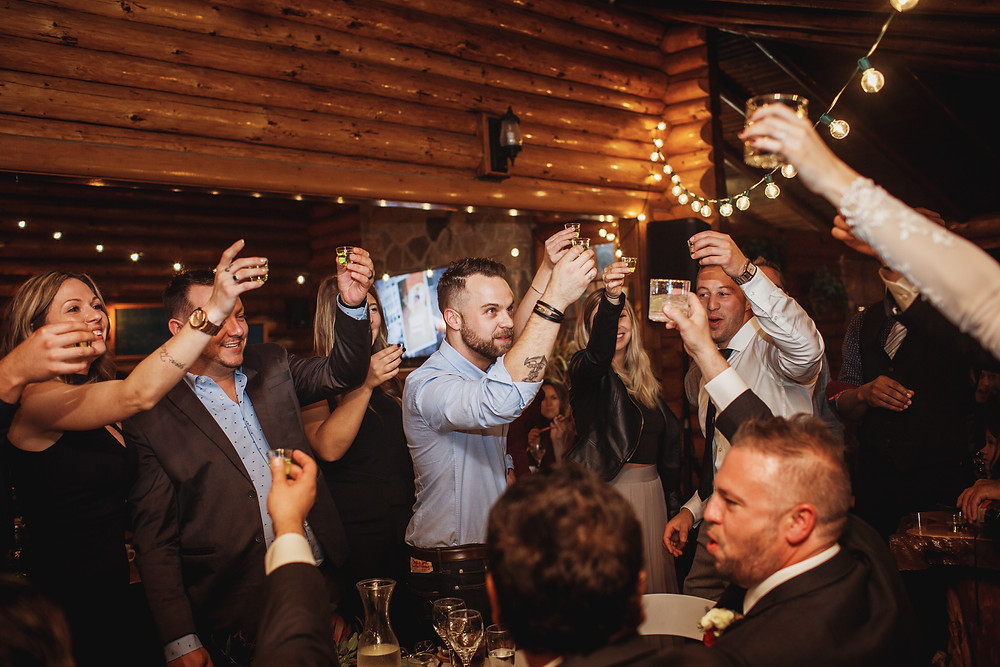 Wedding guests share a shot in order to get the bride and groom to kiss.