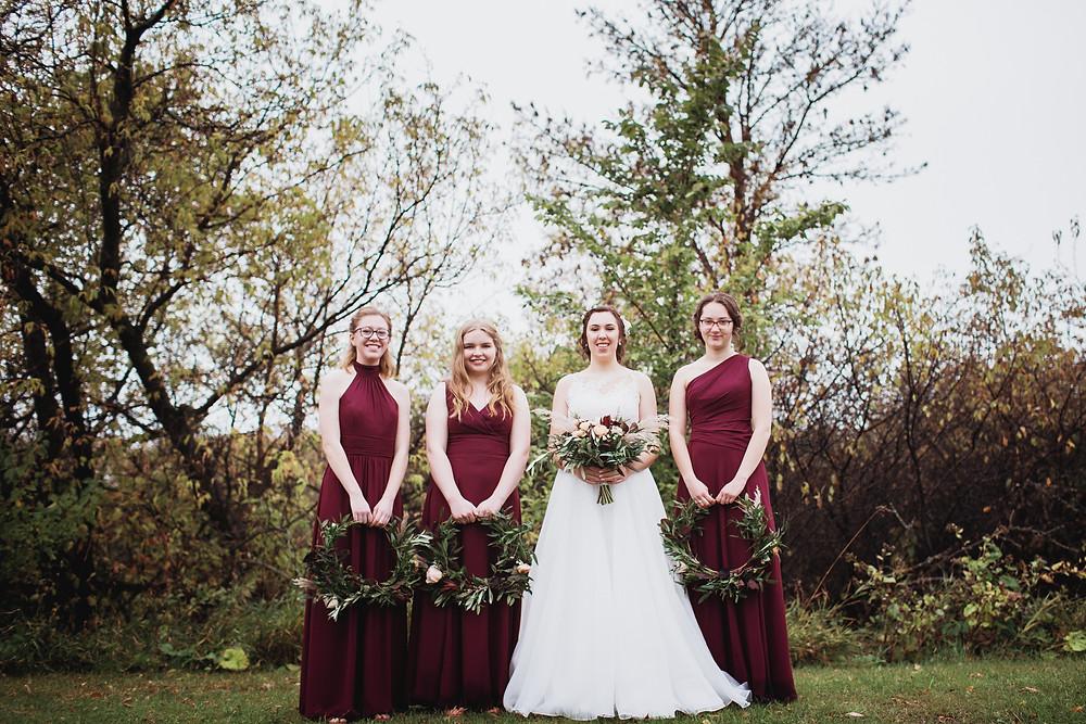 Maroon bridesmaid dresses with flower hoops.