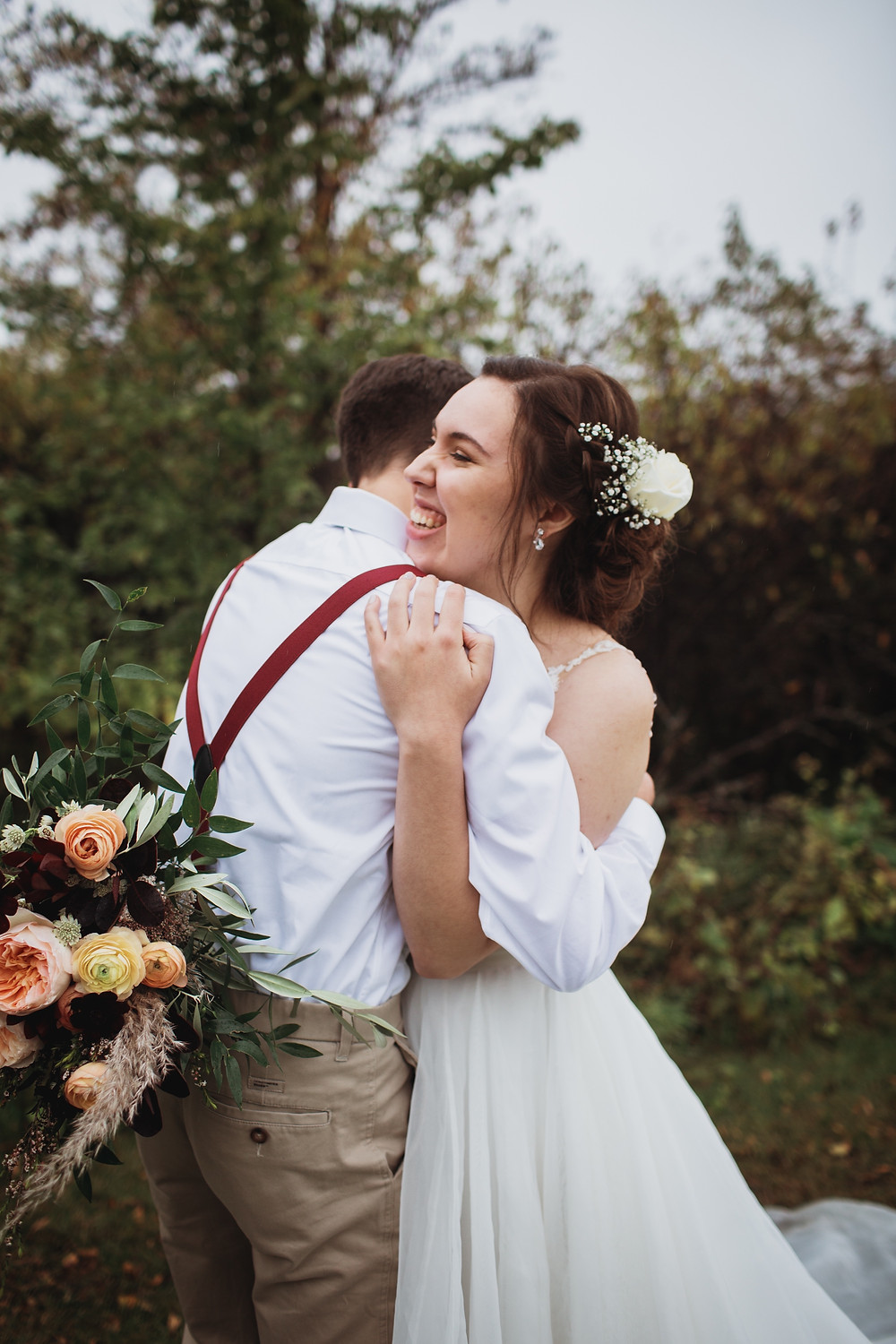 Fall bride and groom embrace on their wedding day in Winkler, Manitoba.