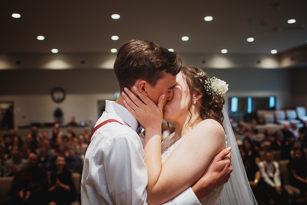 Wedding ceremony - bride and groom kiss as husband and wife.