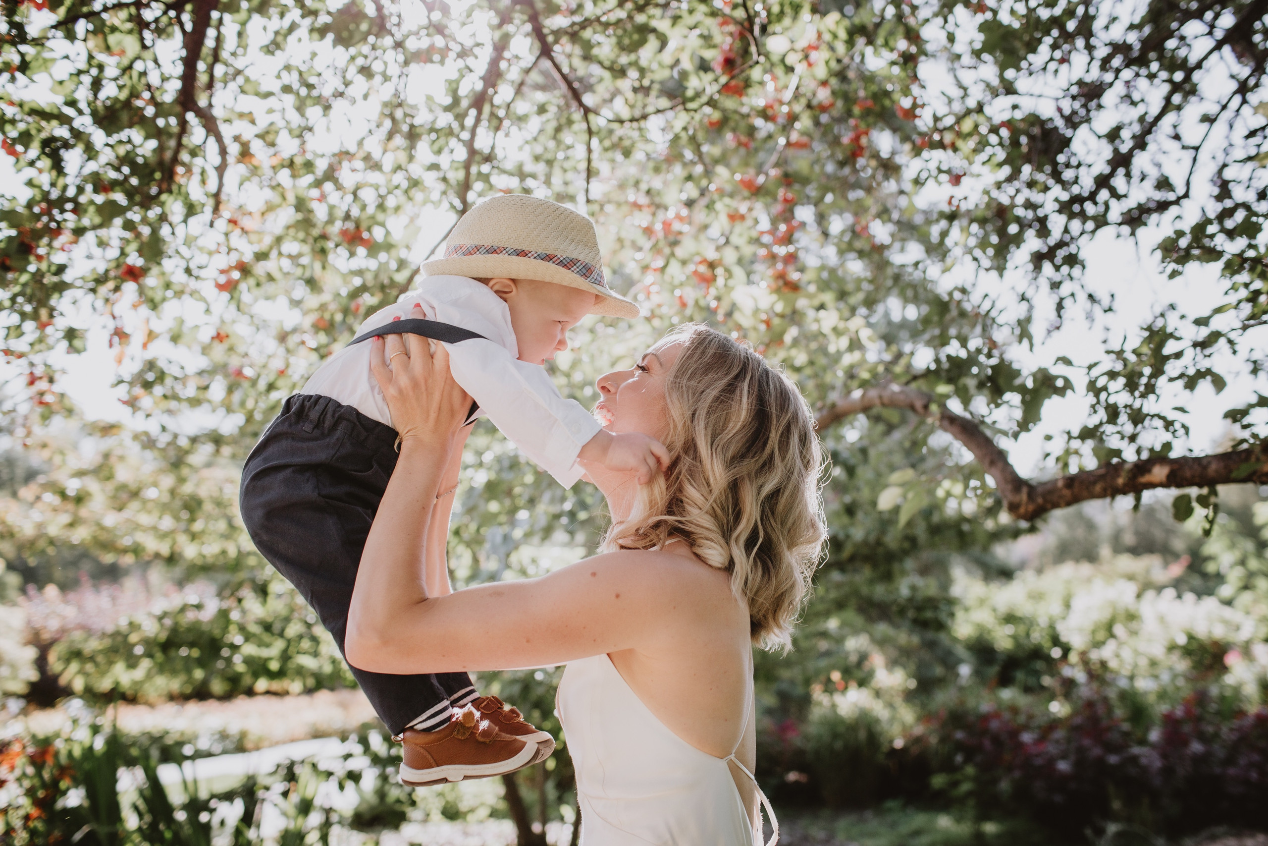 Bride Lifts Up Young Son during wedding day portraits.