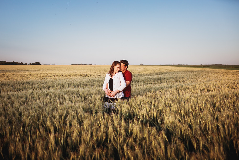 Engaged couple poses in their wheat field during photo session.