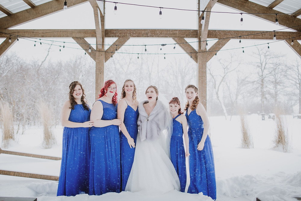 Bridesmaids brave the cold winter wedding day for outdoor portraits.