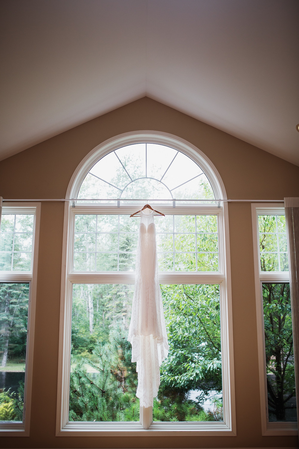 Wilderly bridal gown from LA Collections in Winnipeg, hanging i large living room window.