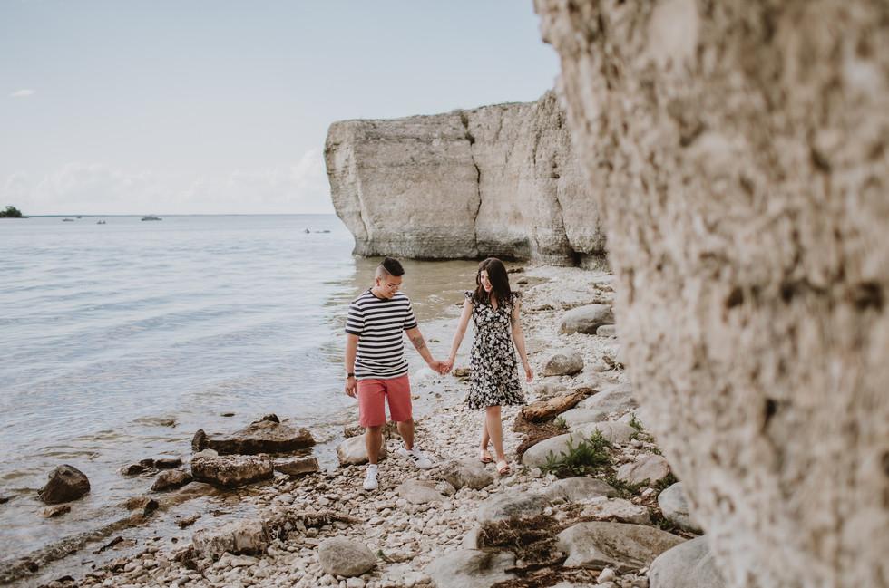 Engaged Couple Walks along Rocky Beach