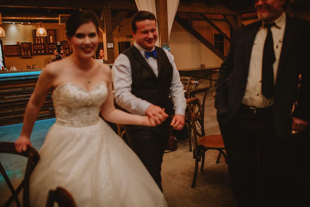 Bride and groom enter wedding reception.