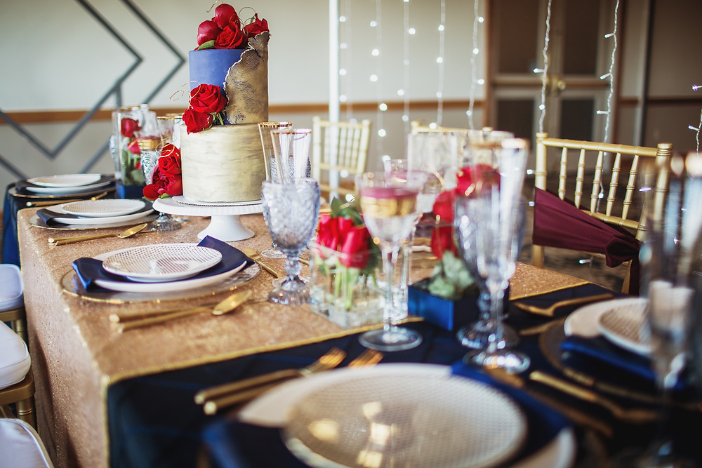 A tablescape inspired my the Marvel universe, designed by GeekChic Decor, feature a gold sequin table runner and navy satin linens, and Chiavari chairs in gold.