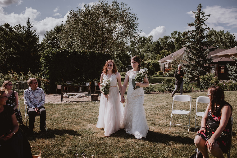 Brides walking down the aisle in backyard micro-wedding.