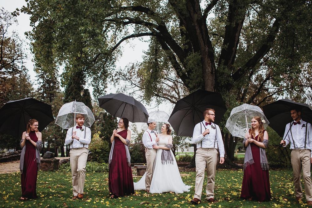 Bridal party under umbrellas during rainy fall wedding