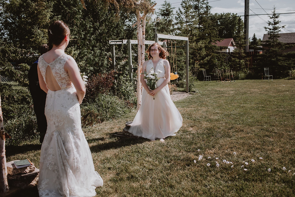 Manitoba wedding couple stands under arch in backyard ceremony.